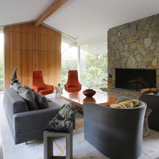Living room - large 1950s open concept concrete floor living room idea in Los Angeles with yellow walls, a standard fireplace, a stone fireplace and a concealed tv