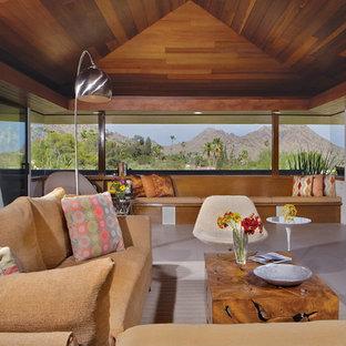 フェニックスの中くらいのミッドセンチュリースタイルのおしゃれなLDK (ベージュの壁、磁器タイルの床、標準型暖炉、石材の暖炉まわり、壁掛け型テレビ、グレーの床) の写真
