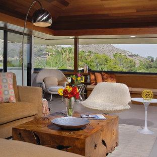 フェニックスの中サイズのミッドセンチュリースタイルのおしゃれなLDK (ベージュの壁、磁器タイルの床、標準型暖炉、石材の暖炉まわり、壁掛け型テレビ、グレーの床) の写真