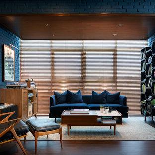Immagine di un soggiorno minimalista di medie dimensioni e stile loft con sala della musica, pareti blu, pavimento in laminato, nessun camino, nessuna TV e pavimento marrone