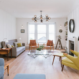 This is an example of a medium sized retro enclosed living room in Cornwall with white walls, light hardwood flooring, no tv, a standard fireplace and a brick fireplace surround.
