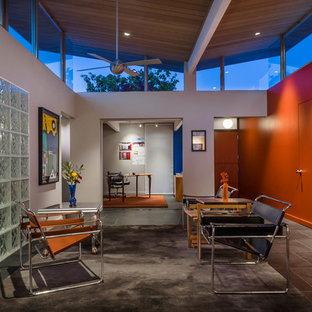 サンフランシスコのミッドセンチュリースタイルのおしゃれなLDK (オレンジの壁、グレーの床) の写真
