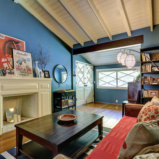 Example of a 1950s medium tone wood floor living room design in Los Angeles with blue walls, a standard fireplace and a wood fireplace surround