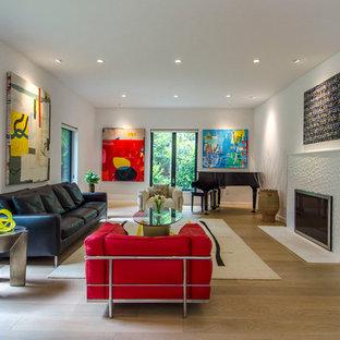 Стильный дизайн: парадная гостиная комната в современном стиле с белыми стенами, светлым паркетным полом, стандартным камином и фасадом камина из плитки - последний тренд