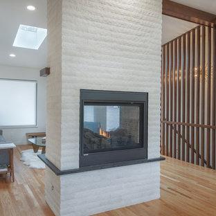 Immagine di un soggiorno minimalista con pareti bianche, parquet chiaro, camino bifacciale, cornice del camino in mattoni, pavimento multicolore e soffitto a volta