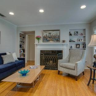 ダラスの中サイズのミッドセンチュリースタイルのおしゃれな独立型リビング (フォーマル、ベージュの壁、淡色無垢フローリング、標準型暖炉、木材の暖炉まわり、内蔵型テレビ、オレンジの床) の写真