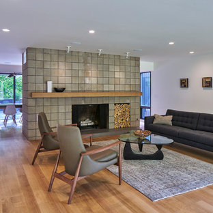 Midcentury living room in Grand Rapids with white walls, light hardwood floors, a standard fireplace, a tile fireplace surround and beige floor.