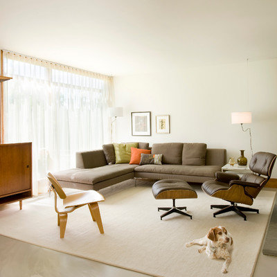 Mid-sized trendy open concept concrete floor and gray floor living room photo in Boston with white walls, a stone fireplace and a concealed tv
