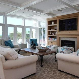 ニューヨークの中サイズのビーチスタイルのおしゃれなLDK (グレーの壁、無垢フローリング、標準型暖炉、コンクリートの暖炉まわり、壁掛け型テレビ、茶色い床) の写真