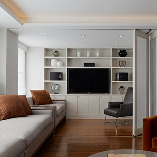 Mid-sized minimalist enclosed dark wood floor and brown floor living room photo in New York with white walls, no fireplace and a media wall