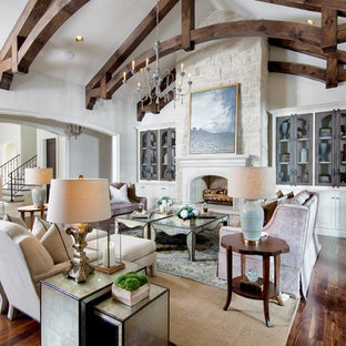 Inspiration for a large mediterranean formal and open concept dark wood floor and brown floor living room remodel in Nashville with beige walls, a standard fireplace, a plaster fireplace and a concealed tv