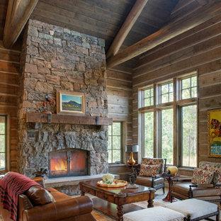 Offenes Rustikales Wohnzimmer mit brauner Wandfarbe, braunem Holzboden, Kamin, Kaminumrandung aus Stein, braunem Boden, freigelegten Dachbalken, gewölbter Decke, Holzdecke und Holzwänden in Sonstige