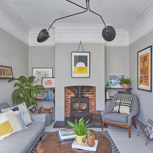 Immagine di un soggiorno nordico con pareti grigie, pavimento in legno verniciato, stufa a legna, pavimento grigio e libreria