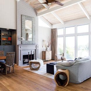 Cette photo montre un salon chic ouvert avec un mur blanc, un sol en bois brun, une cheminée standard, un manteau de cheminée en brique et un sol marron.