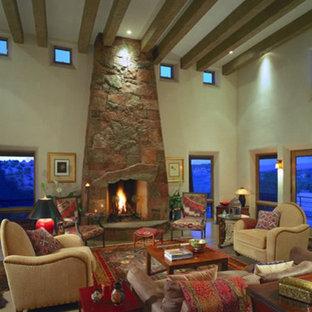 アルバカーキの中くらいのサンタフェスタイルのおしゃれなLDK (フォーマル、ベージュの壁、コンクリートの床、標準型暖炉、石材の暖炉まわり、テレビなし、ベージュの床) の写真