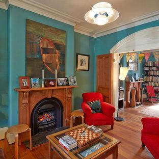 Abgetrenntes Stilmix Wohnzimmer mit blauer Wandfarbe, braunem Holzboden, Kamin und gefliestem Kaminsims in Sydney