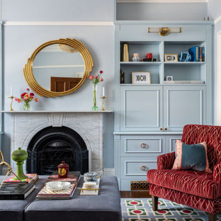 This is an example of a traditional living room in Sydney with a library, blue walls, dark hardwood floors, a standard fireplace and no tv.