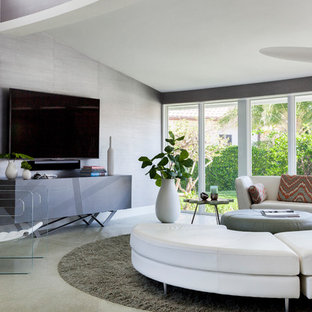 This is an example of a large midcentury open concept living room in Miami with grey walls, a wall-mounted tv and grey floor.