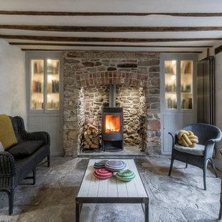 Modelo de salón abierto, campestre, pequeño, con paredes blancas, suelo de piedra caliza, chimenea tradicional y marco de chimenea de piedra