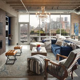 Modelo de salón abierto, industrial, grande, con suelo de cemento, suelo gris, paredes marrones, chimenea lineal, marco de chimenea de madera y televisor colgado en la pared