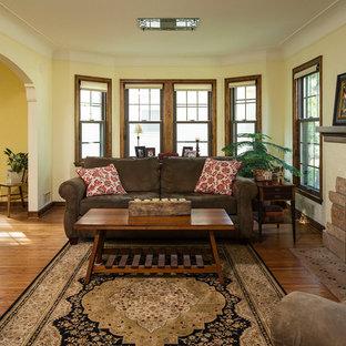 Foto de salón cerrado, tradicional, con paredes amarillas, suelo de madera en tonos medios y chimenea tradicional