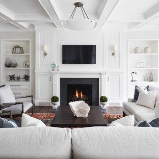 ミネアポリスのビーチスタイルのおしゃれなリビング (白い壁、濃色無垢フローリング、標準型暖炉、壁掛け型テレビ、茶色い床) の写真