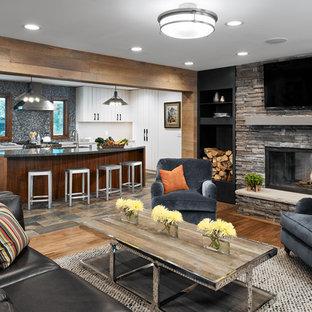 ミネアポリスの大きいビーチスタイルのおしゃれな独立型リビング (フォーマル、マルチカラーの壁、無垢フローリング、標準型暖炉、石材の暖炉まわり、壁掛け型テレビ、茶色い床) の写真