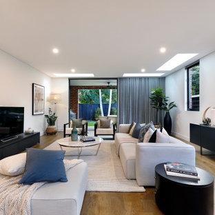 シドニーの中くらいのコンテンポラリースタイルのおしゃれなLDK (白い壁、据え置き型テレビ、無垢フローリング、茶色い床) の写真