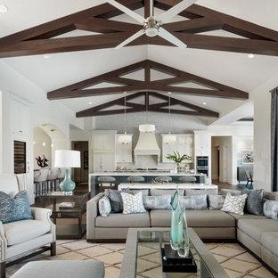 Imagen de salón abierto, clásico renovado, con paredes beige, suelo de madera clara, chimeneas suspendidas, pared multimedia y suelo marrón