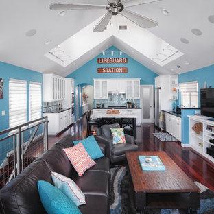 サンディエゴの中サイズのビーチスタイルのおしゃれなLDK (青い壁、濃色無垢フローリング、標準型暖炉、石材の暖炉まわり、据え置き型テレビ) の写真