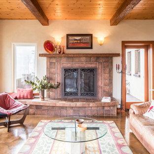 Imagen de salón abierto, mediterráneo, de tamaño medio, con parades naranjas, suelo de cemento, chimenea tradicional, marco de chimenea de baldosas y/o azulejos y suelo marrón