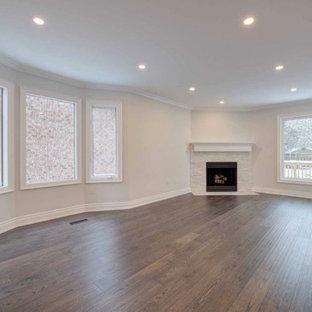 トロントの中くらいのモダンスタイルのおしゃれな独立型リビング (フォーマル、ベージュの壁、濃色無垢フローリング、標準型暖炉、石材の暖炉まわり、テレビなし、茶色い床) の写真