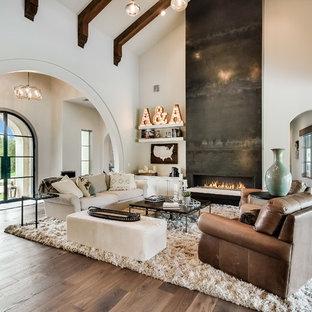 Modelo de salón mediterráneo con paredes blancas, suelo de madera clara, chimenea lineal y suelo beige