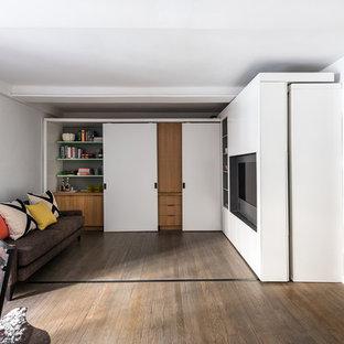 Ejemplo de salón abierto, moderno, pequeño, con paredes blancas, suelo de madera en tonos medios y pared multimedia
