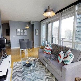 Foto de salón con barra de bar cerrado, actual, pequeño, sin chimenea, con paredes grises, suelo laminado, televisor independiente y suelo amarillo