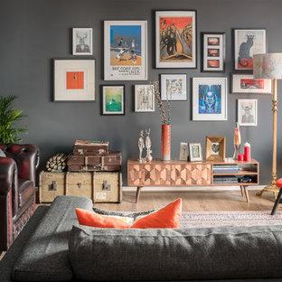 Modelo de salón abierto, bohemio, grande, sin chimenea, con paredes grises, suelo de madera en tonos medios y suelo marrón