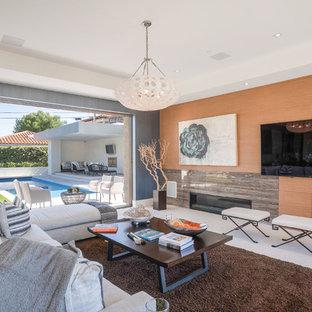 サンディエゴの大きいコンテンポラリースタイルのおしゃれなLDK (フォーマル、オレンジの壁、ライムストーンの床、標準型暖炉、石材の暖炉まわり、埋込式メディアウォール、白い床) の写真
