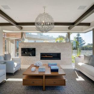 サンディエゴの広いコンテンポラリースタイルのおしゃれな独立型リビング (白い壁、横長型暖炉、タイルの暖炉まわり、白い床、ライムストーンの床、壁掛け型テレビ) の写真