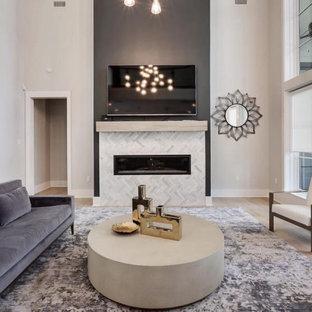 Foto de salón abovedado, moderno, grande, con suelo de madera clara, chimenea tradicional, marco de chimenea de piedra, televisor colgado en la pared y paredes grises