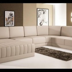 Modern Beige Bonded Leather Sectional Sofa - Your living room will achieve a warmer and genial atmosphere with the presence of the ultra-contemporary design of this modern sectional sofa. A wide chaise provides adequate space where you can relax. Square-shaped end corners provide a resting area for your elbows and features tufted leather. Upholstery is in bonded leather/PVC and can be upgraded to top grain Italian leather via our sales staff.