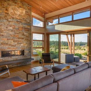 Idéer för ett modernt vardagsrum, med bambugolv, en spiselkrans i sten, beige väggar och en bred öppen spis