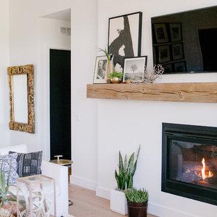 ボイシの広い北欧スタイルのおしゃれなLDK (白い壁、淡色無垢フローリング、標準型暖炉、漆喰の暖炉まわり、壁掛け型テレビ) の写真