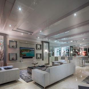 Ejemplo de salón con barra de bar abierto, moderno, grande, sin chimenea, con paredes blancas, suelo de mármol y televisor colgado en la pared