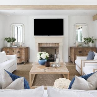 Bild på ett maritimt vardagsrum, med vita väggar, ljust trägolv, en standard öppen spis, en väggmonterad TV och beiget golv