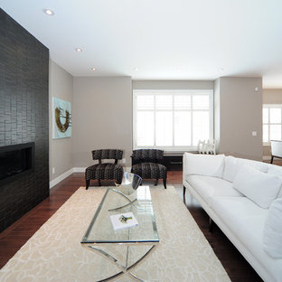 Trendy dark wood floor living room photo in Calgary with beige walls, a ribbon fireplace and a stone fireplace