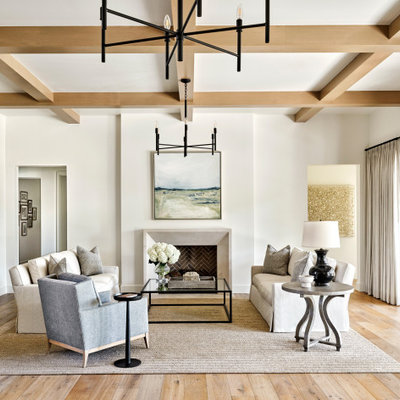 Example of a large transitional formal and open concept light wood floor, beige floor and coffered ceiling living room design in Phoenix with white walls, a standard fireplace, a plaster fireplace and no tv