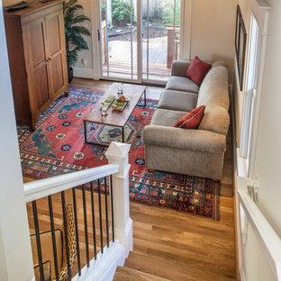 Modelo de salón abierto, de estilo americano, pequeño, sin chimenea, con paredes blancas, suelo de madera en tonos medios y televisor retractable