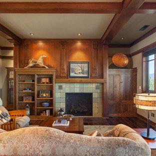 Modelo de salón de estilo americano con paredes beige, suelo de madera oscura, chimenea tradicional, marco de chimenea de baldosas y/o azulejos y suelo marrón