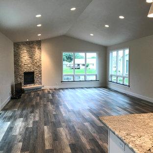 他の地域の中くらいのモダンスタイルのおしゃれなリビングロフト (フォーマル、ベージュの壁、クッションフロア、標準型暖炉、石材の暖炉まわり、テレビなし、マルチカラーの床) の写真