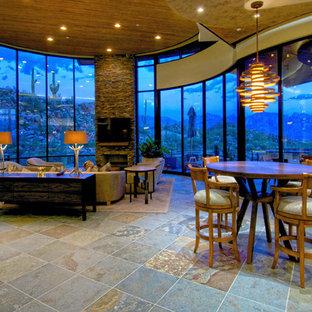 Foto di un grande soggiorno minimal aperto con pareti beige, pavimento in ardesia, camino classico, cornice del camino in pietra, TV a parete e pavimento multicolore